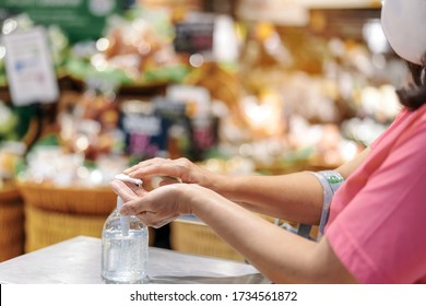Woman washes her hands with clear alcohol gel bottle to prevent the spreading of the corona virus (Covid-19) before entering the supermarket. Shopping during pandemic of Covid-19 concept.