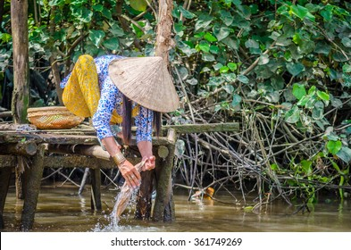 Woman washing clothes in the Mekong river