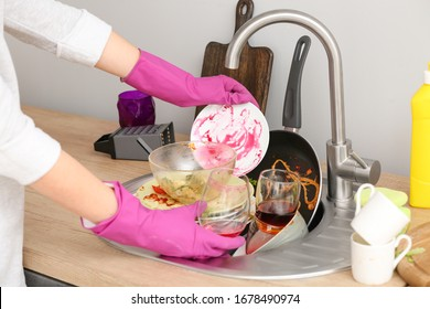 Woman washing dirty dishes in kitchen