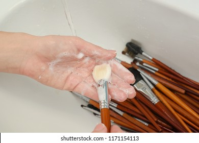 woman is washing dirty makeup brush with soap and foam in the sink