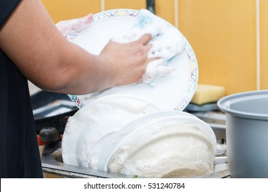 Woman washing dish in the kitchen after dinner, selective focus