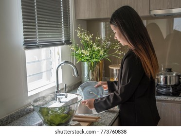 Woman washing the dishes in kitchen