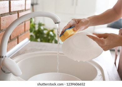 Woman washing dishes in kitchen sink, closeup view. Cleaning chores