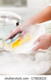 Woman washing the dishes in the kitchen sink area - closeup on hands
