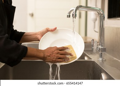 Woman washing the dishes in kitchen sink in the restaurant