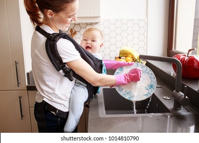 Woman washing dishes while holding her baby in egro carrier backpack