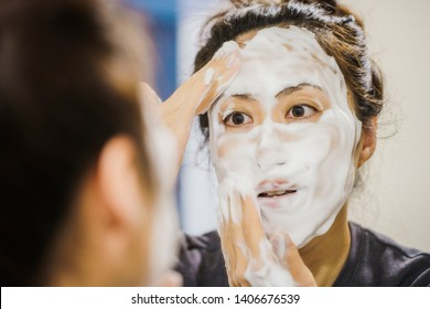 Woman washing face with bubbles