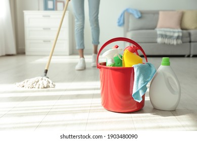 Woman washing floor with mop at home, focus on bucket and cleaning supplies