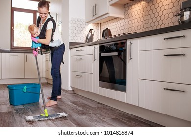 Woman washing floor while holding a baby in ergo baby carrier backpack