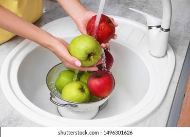 Woman washing fresh apples in kitchen sink, closeup