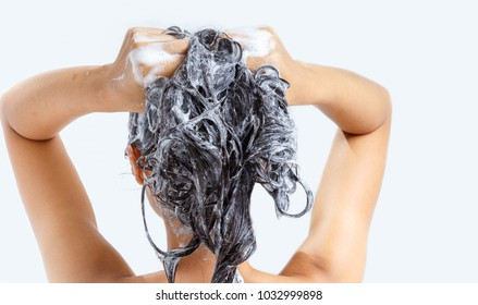 Woman washing hair with shampoo.