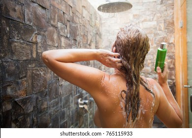 Woman washing hair in shower and holding shampoo bottle