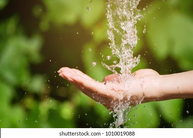 Woman washing hand outdoors. Natural drinking water in the palm. Young hands with water splash, selective focus