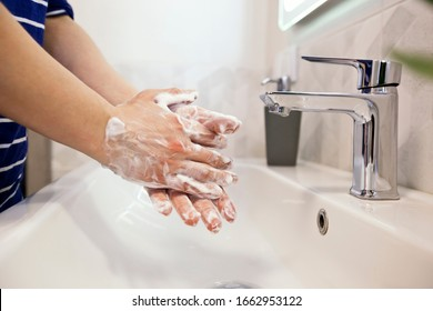 The woman is washing hands with soap in the bathroom