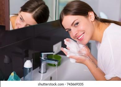 Mulher lavando seu rosto com limpador de espuma pela manhã