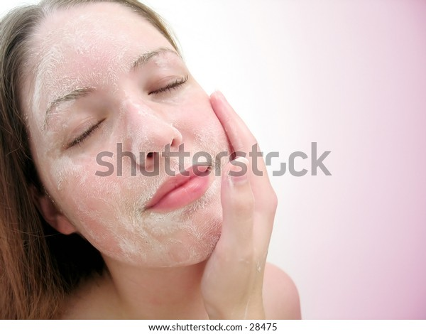 Woman washing her face with soap, eyes closed, small grin. Pink tones.