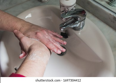 woman washing her hands in a sink of a bathroom