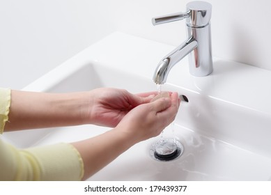 Woman washing her hands with soap under running water from a stainless steel tap on a white ceramic hand basin, health care and hygiene concept
