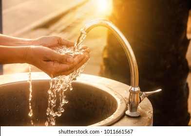 Woman washing her hands at the tap,Water shortage concept