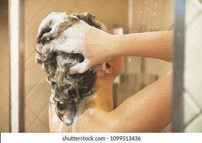 Woman washing her head in the shower.