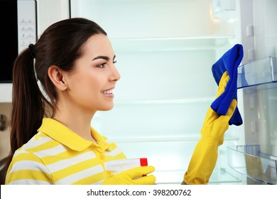 Woman washing refrigerator inside with detergent in the kitchen