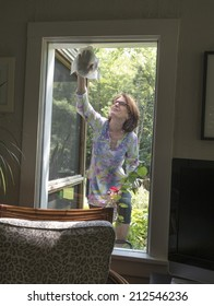 woman washing window from outside of house