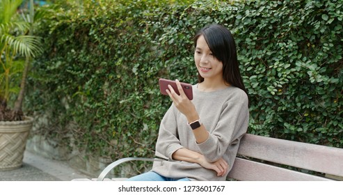 Woman watch on cellphone in park