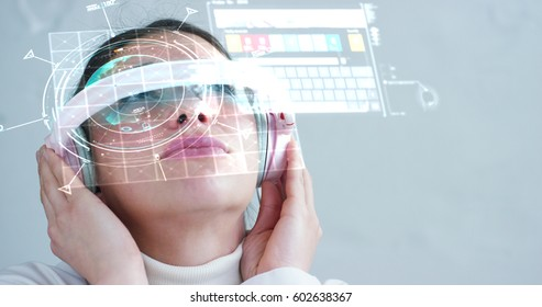 A woman watches with a futuristic look with glasses augmented reality in holography. Concept: immersive technology, future, eyes, and futuristic vision, asian.
