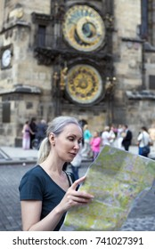 the woman watches the map of the city on background of historical medieval astronomical Clock on the Old Town Hall in Prague, Czech Republic