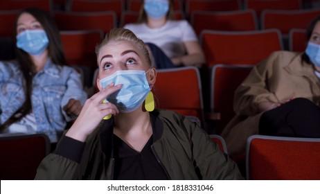 Femme regardant un film sous masque de protection. Médias. Belle jeune femme regarde un film avec intérêt pour le cinéma. Aller au cinéma pendant la pandémie de coronavirus
