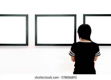 Woman watching blank photo frame on wall art gallery, art exhibition