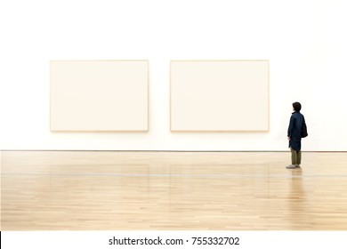 Woman watching blank photo frame on wall art gallery, Art exhibition concept