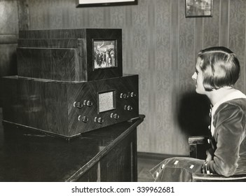 Woman watching a German television with a 14 x 18 centimeter screen. Transmission of live events was still not possible. Instead, events were filmed with moving images and these are broadcast at 25 pi