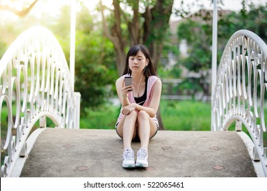woman watching her smart phone in the park.