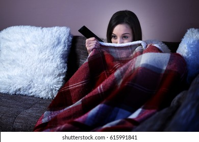 Woman watching horror film at night