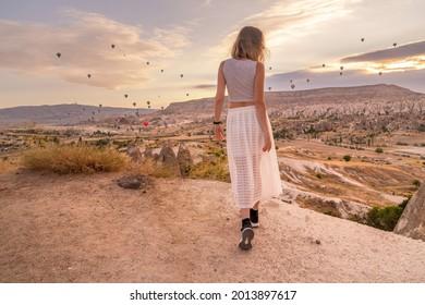 Woman watching hot air balloons on sunrise viewpoint, Cappadocia, Turkey
