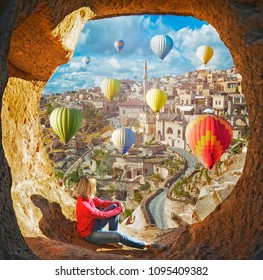 Woman watching  like colorful hot air balloons flying over the valley at Cappadocia, Turkey. Volcanic mountains in Goreme national park.