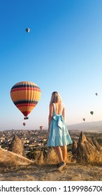 Woman watching like colorful hot air balloons flying over the valley at Cappadocia, Turkey. Romantic scene Cappadocia, Turkey