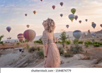 woman is watching on scenery view with rising balloons on sunrise. Girl in gorgeous pink long dress dance on hill looking at large number of air balls. Fabulous Cappadocia mountains landscapes Turkey