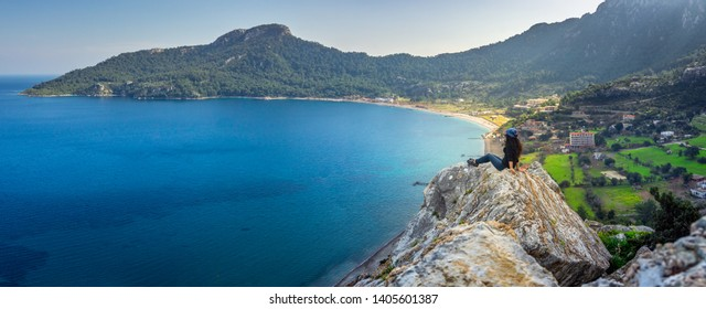 A woman watching the panoramic view of marmaris, on the edge of the cliff. Kumlubuk, Marmaris, Turkey. Amos Ancient city. Amazing coastline. Holiday, travel and tourism concept.
