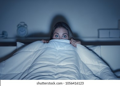 Woman watching a scary horror movie on tv late at night, she is frightened and hiding under the blanket