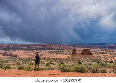 Woman watching stormy sky in Arches national Park, Utah
