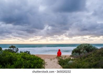 Woman watching sunrise on the beach