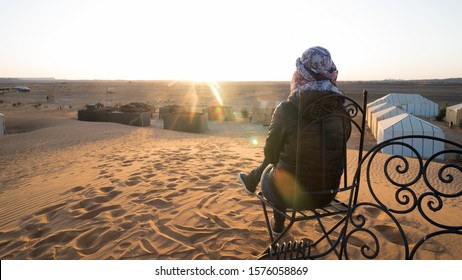 Woman watching the sunrise sitting on a chair in the dunes of the Sahara desert.