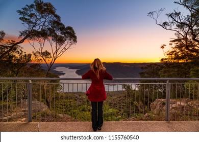 Woman watching the sunset at Burragorang lookout, Nattai Australia