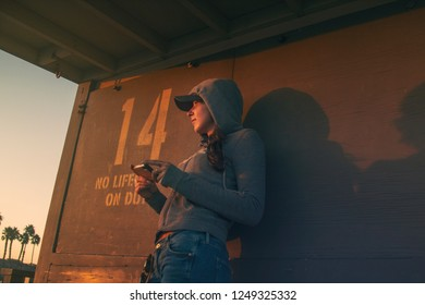 Woman watching the sunset on a lifeguard tower in Southern California