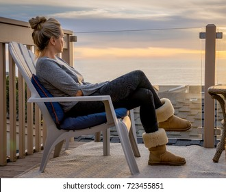 Woman watching sunset over the ocean - Stock photo