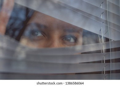 Woman  watching through window blinds. Portrait of young thoughtful female with brown eyes observing through window jalousie