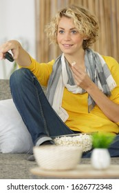 woman watching tv alone zapping the channel