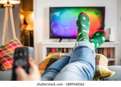 Woman watching tv close up of female feet in front of tv woman hand holding remote controller while watching tv